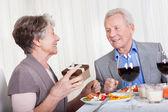 Starší muž dává dárek pro starší žena — Stock fotografie