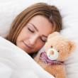Young Beautiful Woman Sleeping On Bed With Her Teddy Bear — Stock Photo #23527717