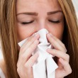 Close-up Of A Young Woman Sneezing In To Tissue — Stock Photo