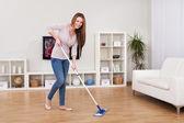 Mladá žena čištění podlahy — Stock fotografie