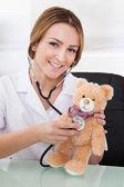 Médica examinando o ursinho de pelúcia — Foto Stock