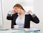 Businesswoman Stretching In Office — Stock Photo