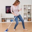 图库照片: Young Woman Dancing While Cleaning Floor