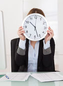 Businesswoman Holding Clock In Front Of Her Face In Office — Stock Photo