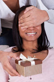 Young Man Surprising Woman With Gift Box — Stock Photo