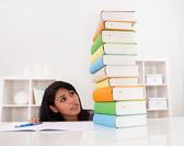 Shocked Woman Looking At Stack Of Books — Stockfoto