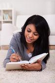 Jeune femme écrivant dans le journal — Photo