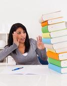 Chocado mulher olhando para a pilha de livros — Foto Stock