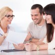 Happy Doctor Discussing With Couple — Stock Photo #26667157