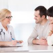 Happy Doctor Discussing With Couple — Stock Photo #26667297