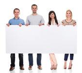 Groep vrienden houden plakkaat — Stockfoto