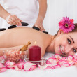 Happy woman getting hot stone therapy — Stock Photo
