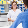 Female Pharmacist In Pharmacy With A Client — Stock Photo