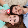 Happy young couple lying on back — Stock Photo