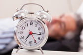 Alarm Clock In Front Of Man Sleeping — Stock Photo