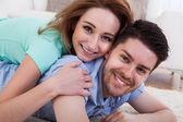 Glückliches junges paar auf vorne liegend — Stockfoto