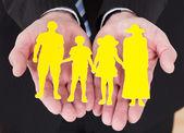 Männliche hand hält familie ausschnitt-form — Stockfoto