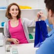 Cashier Handing Over Shopping Bag To Customer — Stock Photo