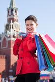 Joven sosteniendo bolsas y mostrando la tarjeta de crédito — Foto de Stock