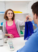 Cashier Handing Over Shopping Bag To Customer — Stockfoto