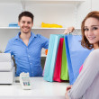 Stock Photo: Cashier Handing Over Shopping Bag To Customer