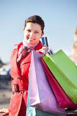 Ung kvinna håller påsar och visar kreditkort — Stockfoto