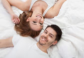 Portrait of happy young couple lying on bed — Stock Photo