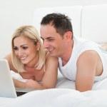 Happy Couple Lying On Bed Using Laptop — Stock Photo
