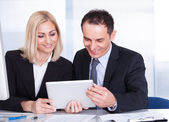 Businessman And Businesswoman Looking At Digital Tablet — Stock Photo
