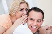Mid-adult man and woman sharing a secret — Stock Photo