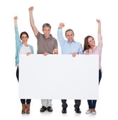 Group Of Happy People Holding Placard — Stockfoto