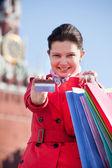 年轻女子举行购物袋和显示信用卡 — 图库照片