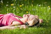 Woman Lying On Grass Listening Music — Stock Photo