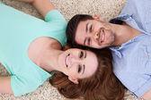 Heureux jeune couple allongé sur le dos — Photo
