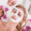 Foto Stock: Cosmetician Applying Facial Mask On Face Of Woman