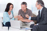 Consultant Offering Business Card To Couple — Stock Photo