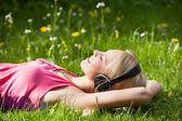 Jonge vrouw liggen op gras en luisteren naar muziek met een hoofdtelefoon — Stockfoto