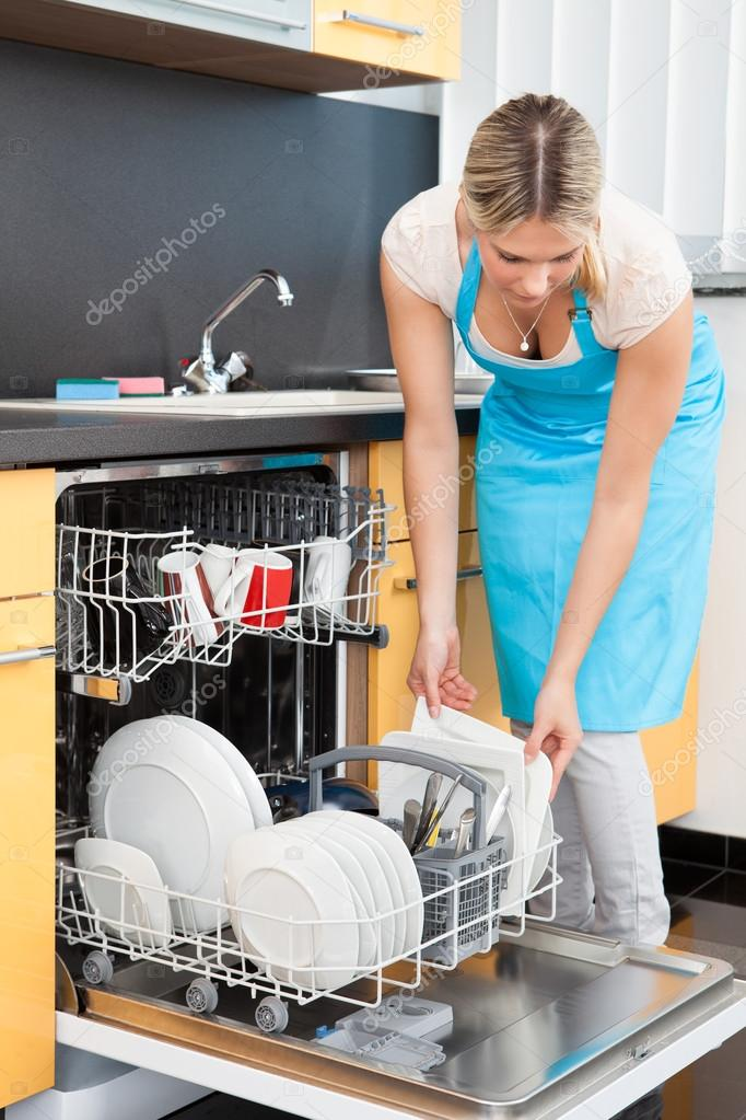 Dishes In Dishwasher ~ Woman putting dishes in the dishwasher — stock photo