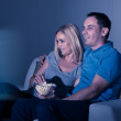 Couple Watching Television And Eating Popcorn At Home — Stock Photo #29295063