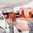 Stock Photo: Young plumber fixing a sink in bathroom