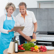Mature Couple Using Tablet While Cooking — Stock Photo #29295659