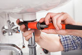 Young plumber fixing a sink in bathroom — Stock Photo