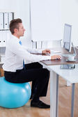 Businessman Sitting On Pilates Ball And Using Computer — Stock Photo