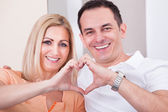Happy Mid-adult Couple Forming Heart Shape Together — Stock Photo