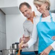 Stock Photo: Happy Mature Couple Cooking Food In Kitchen