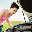 Stock Photo: WomLooking Under Hood Car