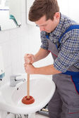 Portrait of male plumber pressing plunger — Stock Photo