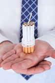 Empresario sosteniendo cigarrillos atados con cuerda y mecha — Foto de Stock
