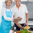 Mature Couple Using Tablet While Cooking — Stock Photo