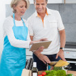 Stock Photo: Mature Couple Using Tablet While Cooking